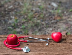 Stethoscope,apple  and  red  heart  on  old  wooden  surface  with  nature  blurry  background  for  World  Heart  Day  concept