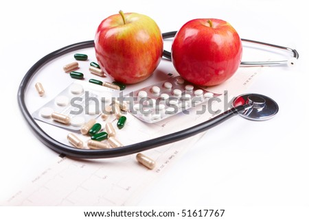 stethoscope, apples, pills and EKG chart over white background used as health and healthy lifestyle symbol.