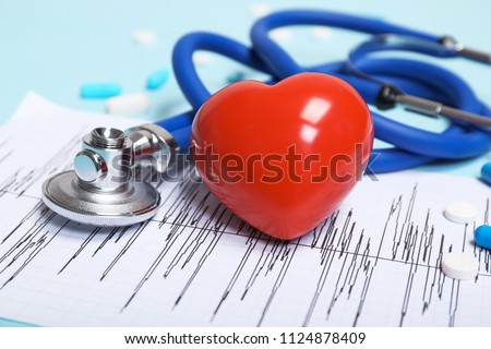 Stethoscope, cardiogram and heart model on table. Cardiology service