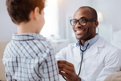 Stethoscope exam. Attractive cheerful male doctor listening to boy while putting on glasses and using stethoscope