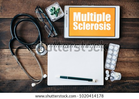 Stethoscope, eyeglass, blank notebook, medicine and digital tablet with MULTIPLE SCLEROSIS word