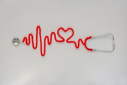 Stethoscope forming heartbeat with its cord. Healthcare concept. World Heart Day. Space for text. Soft focus. Top view.