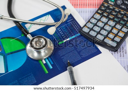 Stethoscope, graph chart, pen and calculator on table