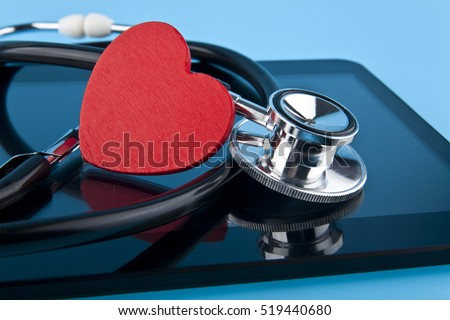 stethoscope, heart and tablet on blue background closeup #519440680
