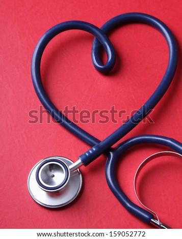 Stethoscope isolated on red background - stock photo