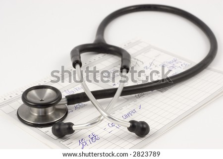 Stethoscope lying on a medical report on a white desk