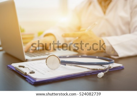 Stethoscope on a prescription clipboard and Laptop on desk,Doctor working an Exam, Healthcare and medical concept,test results in background,vintage color,selective focus