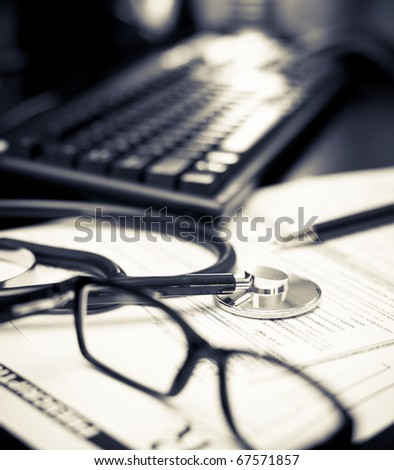 Stethoscope on a prescription form with glasses pen and keyboard, very shallow DOF
