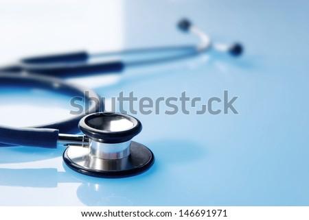 Stethoscope on blue, reflective background
