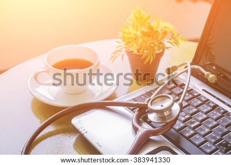 Stethoscope on laptop keyboard,stethoscope on the keyboard of pc,Medical Stethoscope Resting on Desk,relax time doctor,selective focus,vintage color.morning light