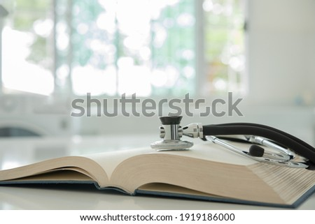 stethoscope on medical guide book for doctor learning treatment at hospital.  medical education learning concept.