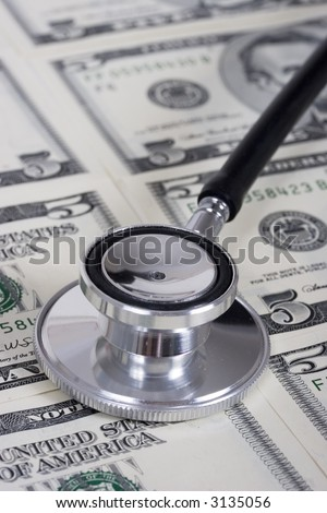 Stethoscope on money background of five dollar bills