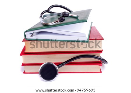 Stethoscope on the stack of books isolated on white