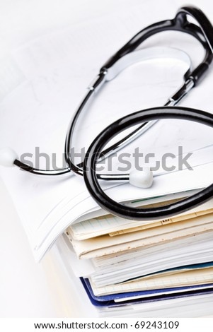 stethoscope on the stack of paper - stock photo