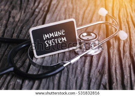 Stethoscope on wood with immune system word as medical concept. #531832816