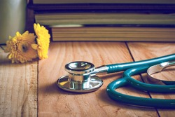 stethoscope on wooden table ,vintage tone.