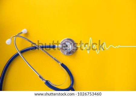 stethoscope on yellow background with cardiogram, health concept
