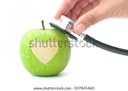 Stethoscope over a heart shape carved in an apple