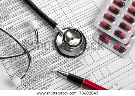 Stethoscope, pen and pill capsules resting on medical examination notes or patient record form - stock photo