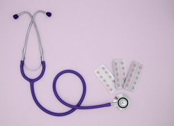 Stethoscope, three blisters with pink medical pills on pink background with copy space. Medical flat lay.