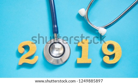 Stethoscope w/ 2019 gold wooden number on blue background. Happy New Year for healthcare and medical banner/calendar cover. Creative idea for new trend in medicine treatment and diagnosis concept.