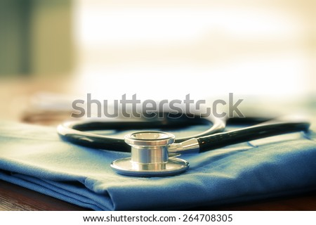 Stethoscope with blue doctor coat on wooden table with shallow DOF evenly matched and background