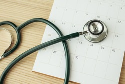 Stethoscope with calendar page date on wood table background doctor appointment medical concept