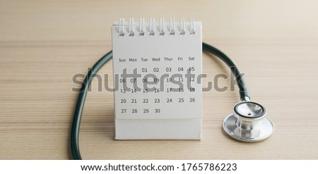 Stethoscope with calendar page date on wood table background doctor appointment medical concept stock photo