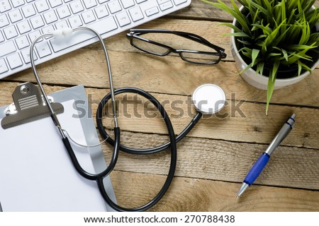 Stethoscope with clipboard and keyboard. Stethoscope,clipboard ,keyboard and green plant on wooden background