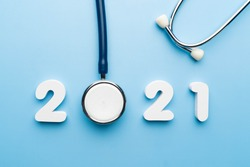 Stethoscope with 2021 number on blue background. Happy New Year for health care and medical banner/calendar cover. Creative idea for new trend in medicine treatment and diagnosis concept.