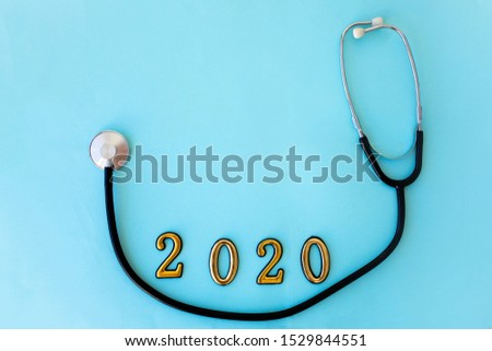 Stethoscope with 2020 number on blue background. Happy New Year for health care and medical banner/calendar cover. Top view , copy space. Medicine treatment and diagnosis concept.