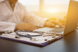 Stethoscope with prescription clipboard and Laptop ,Doctor working an Exam, Healthcare and medical concept,test results in background,vintage color,selective focus