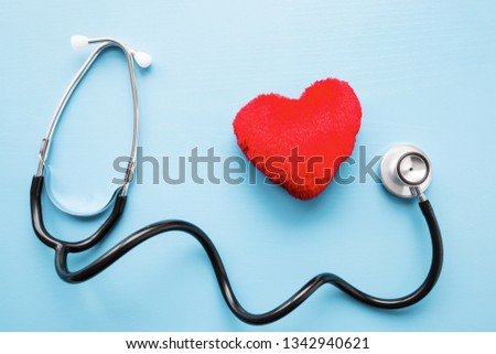 Stethoscope with red heart on pastel blue table. Doctor tool for heartbeat listening. Healthcare concept.  #1342940621