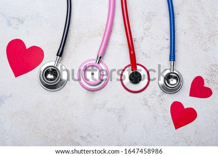 Stethoscopes and hearts on light background. Cardiology concept
