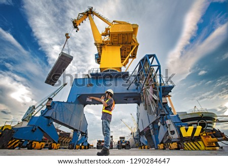 stevedore foreman and or supervisor, loading master takes control in loading discharging operation by walkie talkie and device on line, port operation working under control at quayside Сток-фото ©