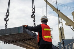 stevedore handle gang works on the ship with lifting gears to carry on steel cargo in the port terminal