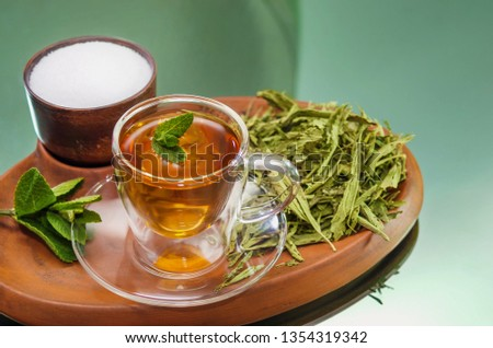 Stevia dry leaves and Stevia sweetener in clayware on mirror background. Stevia have Stevioside (Steviol glycosides) extracted from its leaves. Stevia herb infusion. No sugar added. Healthy concept.