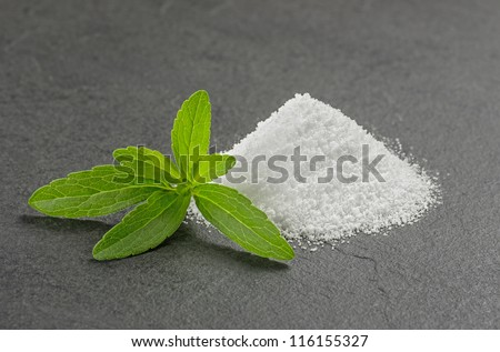 Stevia leaves with stevia powder on a slate plate