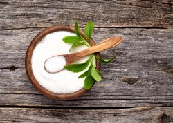 Stevia rebaudiana, sweet leaf sugar substitute in wooden  bowl on wooden background.