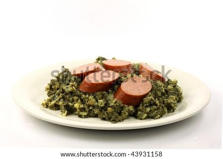 stew of potatoes and kale with smoked sausage on a white plate