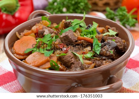 Stew with beef, vegetables and prunes in a saucepan, close-up, horizontal