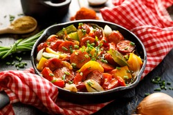 Stew with peppers and sausage in a cast iron skillet on a black background, close up. Traditional Hungarian dish called lecho