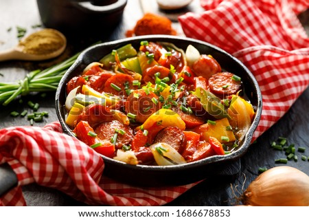 Stew with peppers and sausage in a cast iron skillet on a black background, close up. Traditional Hungarian dish called lecho Foto d'archivio ©