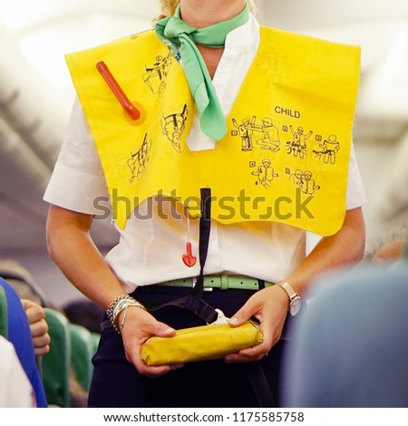 Stewardess in the cabin passenger airplane instructs passengers on safety measures in the event of an emergency