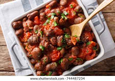 Stewed broad beans in tomato sauce with herbs and spices close-up on the table. horizontal top view from above