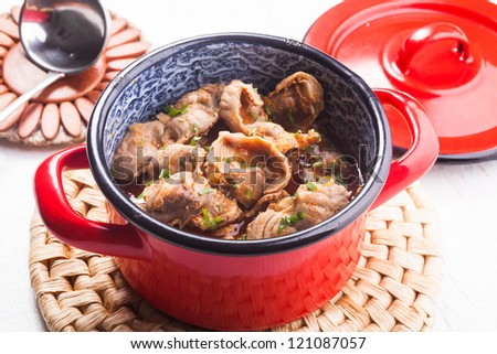 Stewed chicken gizzards in red pan on the mat