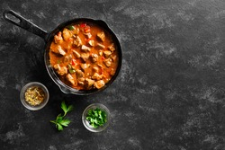 Stewed chicken livers in frying pan over black stone background with free text space. Top view, flat lay