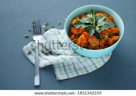 Stewed cooked pumpkin in a deep blue plate, decorated with parsley and pumpkin seeds stands on a textile napkin and a fork lies next to it on a dark background. Photo stock ©