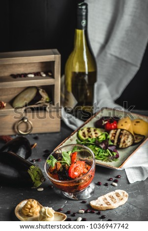 Stewed eggplants, tomatoes, spicy sauce in bowl. Grilled vegetables for Lenten menu, ingredients in box, bottle of wine and napkin in background. Beautiful serve for pub or tavern, healthy lifestyle