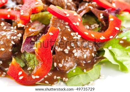 Stewed meat with pepper, lettuce and sesame seeds - stock photo